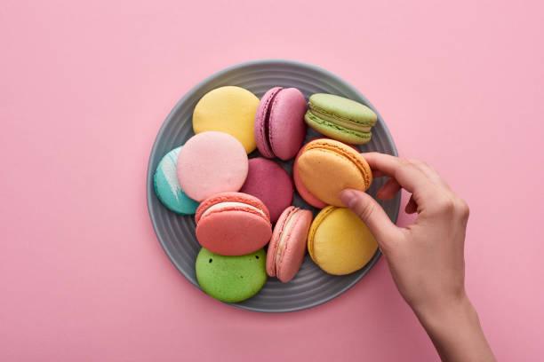 vista cortada da mão fêmea perto da placa com os macaroons franceses deliciosos coloridos no fundo cor-de-rosa - macaroon - fotografias e filmes do acervo
