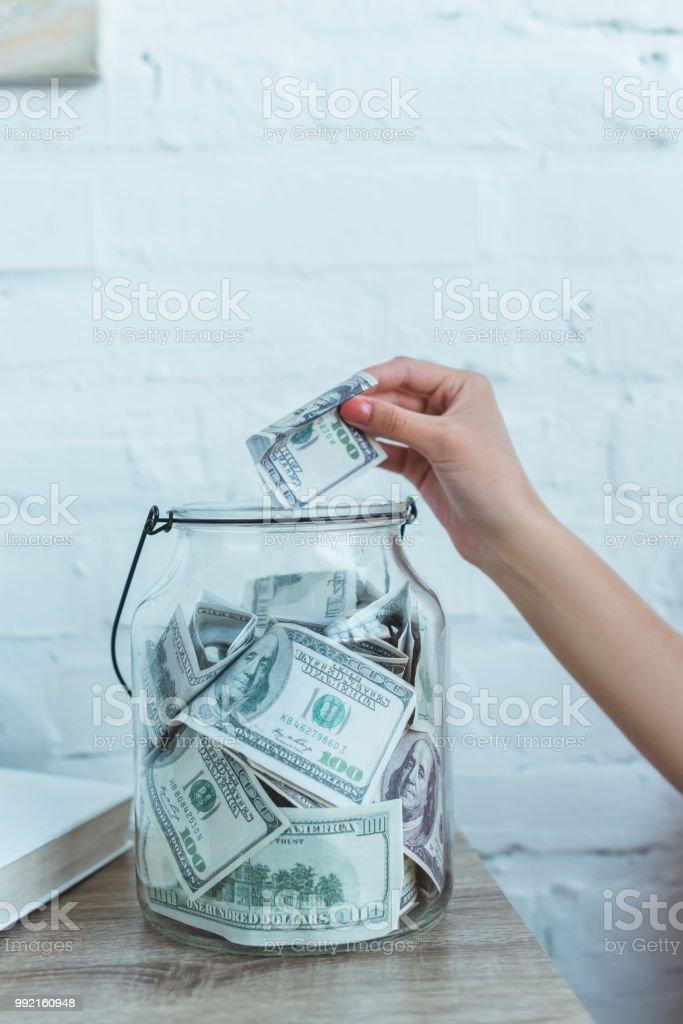 recadrée vue de femelle main mise dollar billets en pot de verre photo libre de droits