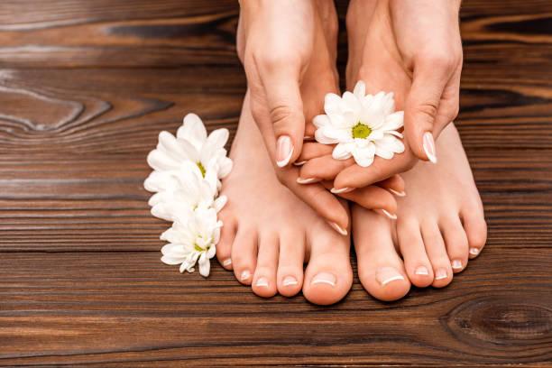 blick auf weibliche hände und füße mit medizin und pediküre auf holzoberfläche beschnitten - fußpflege stock-fotos und bilder