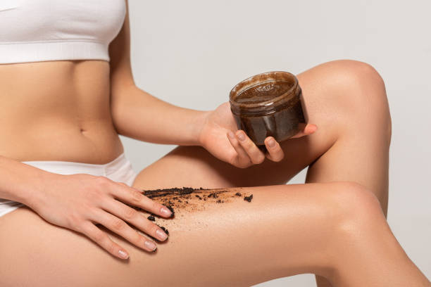 cropped view of girl applying coffee scrub from plastic container, isolated on grey stock photo