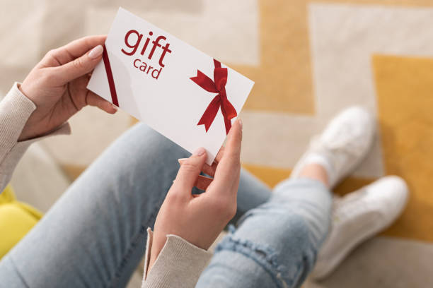 Cropped view of girl holding gift card with red bow stock photo