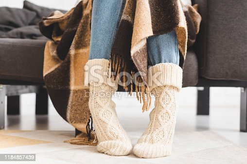 cropped view of girl in knitted socks sitting in blanket on sofa