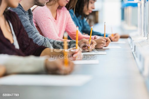 Cropped view of a multiracial group of young men and women sitting in a row at a table, writing with pencils on paper.  They are taking a test or filling out an application.  Focus is on the hand of the young man in the middle in the gray shirt.