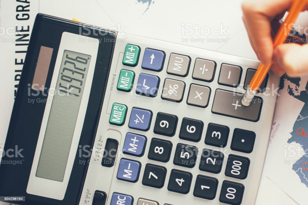 Cropped View of Hand Computing on Calculator stock photo