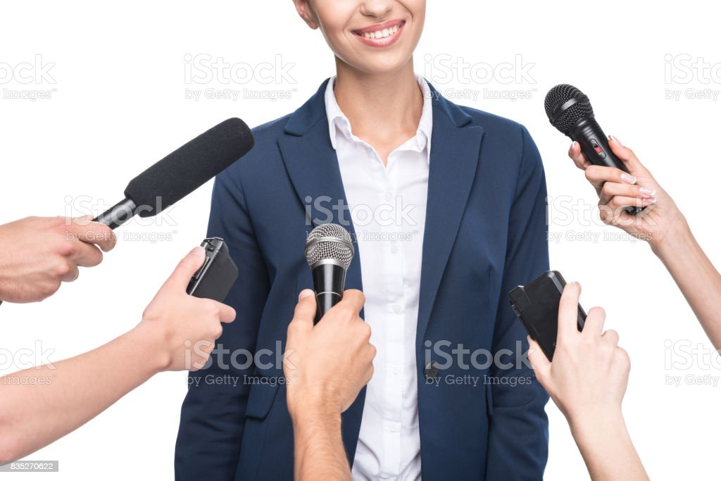 cropped view of journalists with microphones interviewing smiling businesswoman, isolated on white stock photo