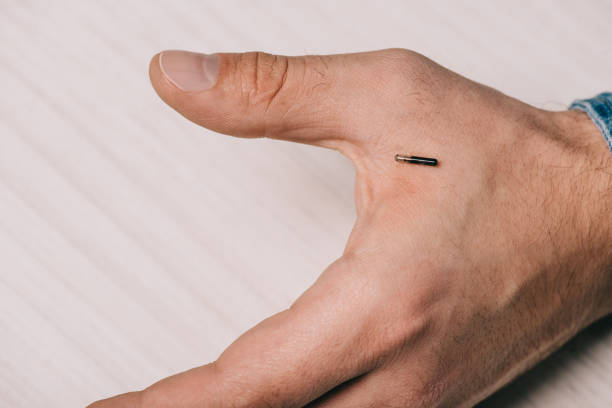 cropped view of male hand with microchip on table cropped view of male hand with microchip on table implant stock pictures, royalty-free photos & images
