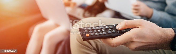 cropped view of man holding remote control in hand near family