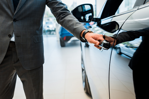 cropped view of man opening car door in car showroom