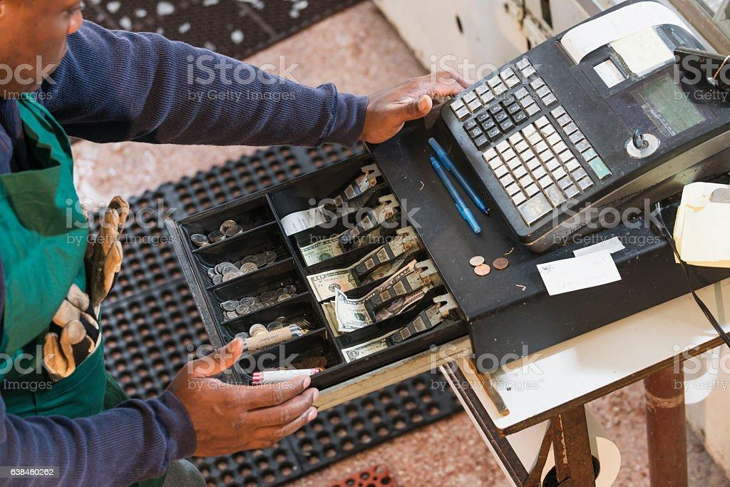 Cropped view of man using old cash register - foto de acervo