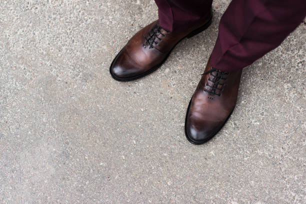 blick auf mann mit ganzen geschnittene leder oxford schuhen beschnitten - schuhe auf englisch stock-fotos und bilder