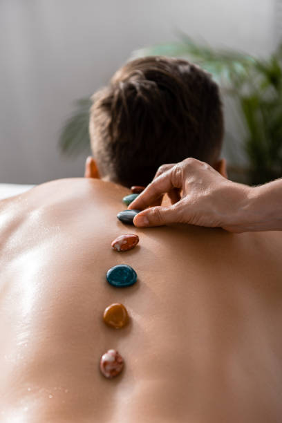 cropped view of masseur and shirtless man with stones on back cropped view of masseur and shirtless man with stones on back crystal healing stock pictures, royalty-free photos & images
