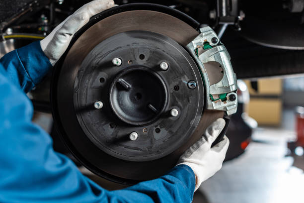 cropped view of mechanic adjusting assembled disc brakes with brake caliper stock photo