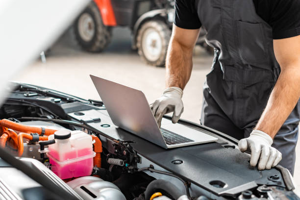 cropped view of mechanic using laptop near car engine compartment stock photo