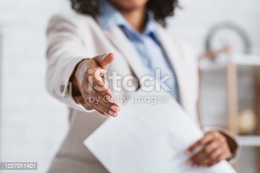 Cropped view of young African American businesswoman holding out her hand for handshake at office