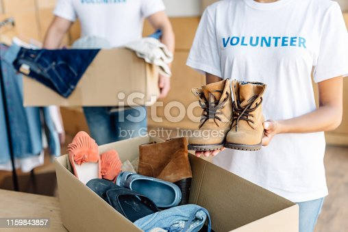 cropped view of multicultural volunteers unpacking cardboard boxes with clothes and footwear
