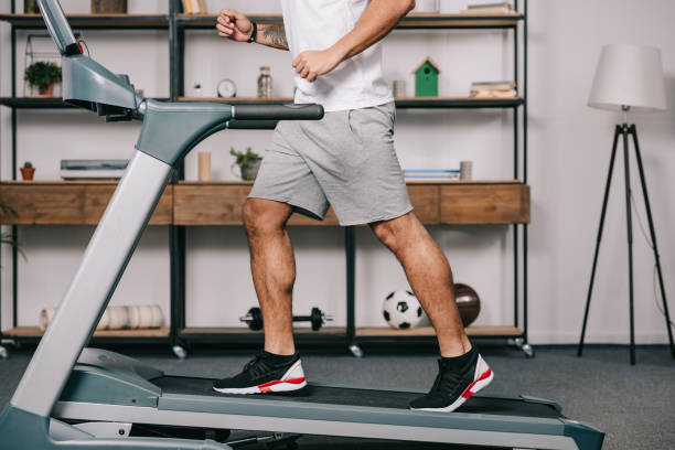 cropped view of muscular sportsman running on treadmill cropped view of muscular sportsman running on treadmill treadmill stock pictures, royalty-free photos & images