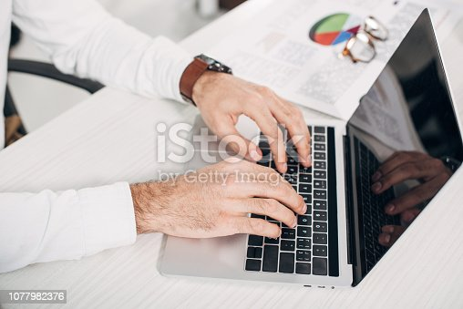 cropped view of office manager typing on laptop keyboard in office