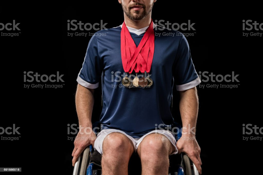 cropped view of paralympic in wheelchair with gold medals on his neck isolated on black stock photo