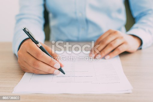 istock Cropped View of Person Completing Application Form 665736922