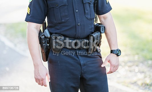 Cropped view of a police officer's waist. He is wearing his equipment belt with gun holster, handcuffs, radio and other gear. He is an Hispanic mid adult man in his 30s standing outdoors.