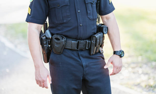 Cropped view of police officer's belt Cropped view of a police officer's waist. He is wearing his equipment belt with gun holster, handcuffs, radio and other gear. He is an Hispanic mid adult man in his 30s standing outdoors. police uniform stock pictures, royalty-free photos & images