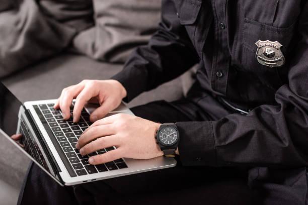 przycięty widok policjanta wpisującego na klawiaturze laptopa - policja zdjęcia i obrazy z banku zdjęć