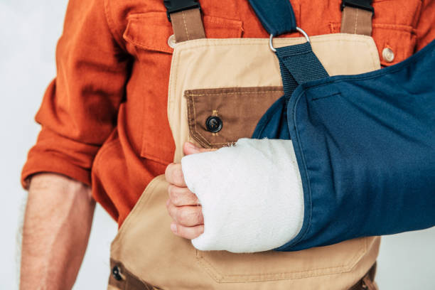 cropped view of repairman with broken arm and bandage on white background stock photo
