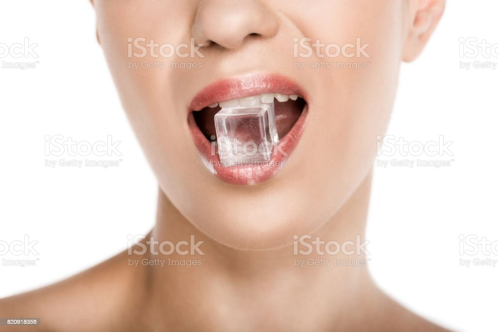 cropped view of seductive woman holding ice cube in mouth, isolated on white - foto stock
