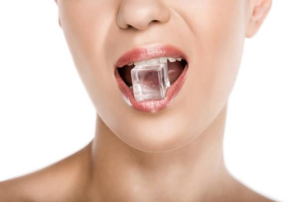verkürzte ansicht verführerische frau mit eiswürfel im mund, isoliert auf weiss - menschlicher mund stock-fotos und bilder