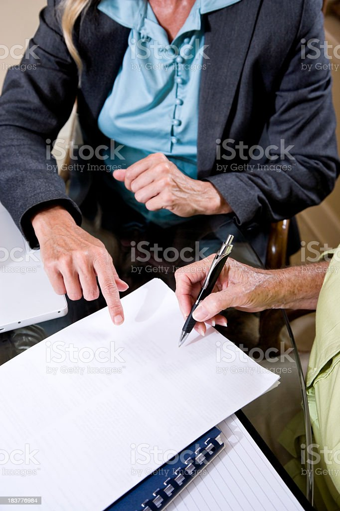 Cropped view of senior woman signing contract stock photo