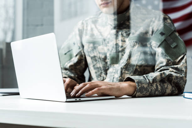 cropped view of soldier in camouflage uniform using laptop - tropa imagens e fotografias de stock