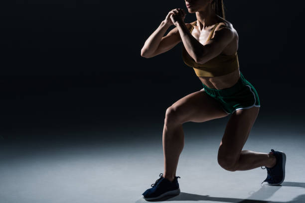 cropped view of sporty female bodybuilder doing lunges, on black - lunge stock photos and pictures