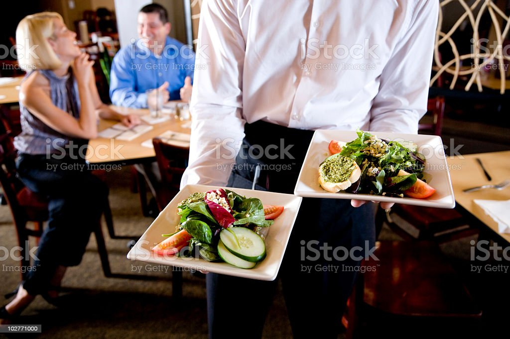 Cropped view of waiter holding salad plates in restaurant royalty-free stock photo