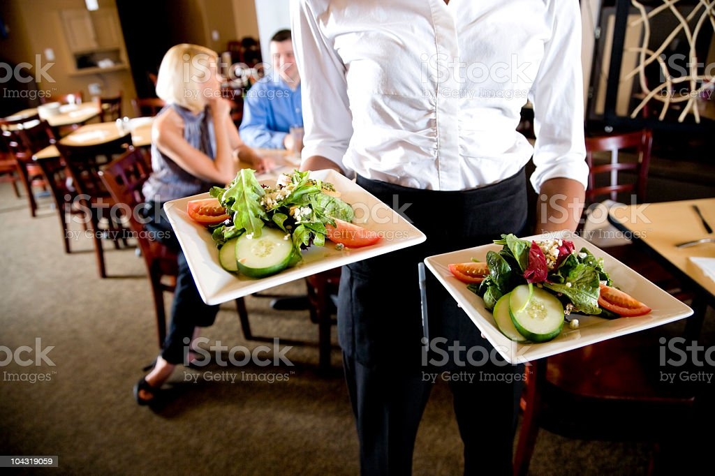 Cropped view of waitress holding salad plates in restaurant royalty-free stock photo