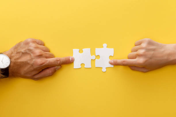 cropped view of woman and man matching pieces of white jigsaw puzzle on yellow background - puzzle foto e immagini stock