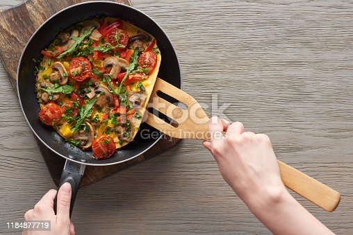 cropped view of woman cooking omelet with mushrooms, tomatoes and greens on frying pan with wooden shovel