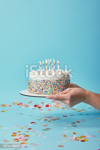 istock Cropped view of woman holding delicious birthday cake with candles on blue background with confetti 1070159202