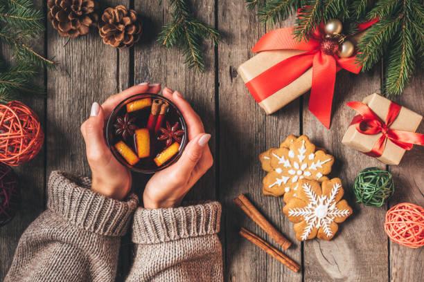 bijgesneden beeld van vrouw met glas met warme glühwein op houten achtergrond met giften van kerstmis - gluhwein stockfoto's en -beelden