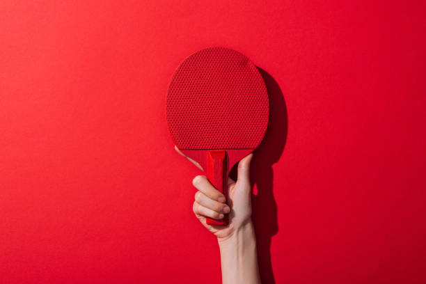 cropped view of woman holding ping pong racket on red - table tennis racket stock pictures, royalty-free photos & images
