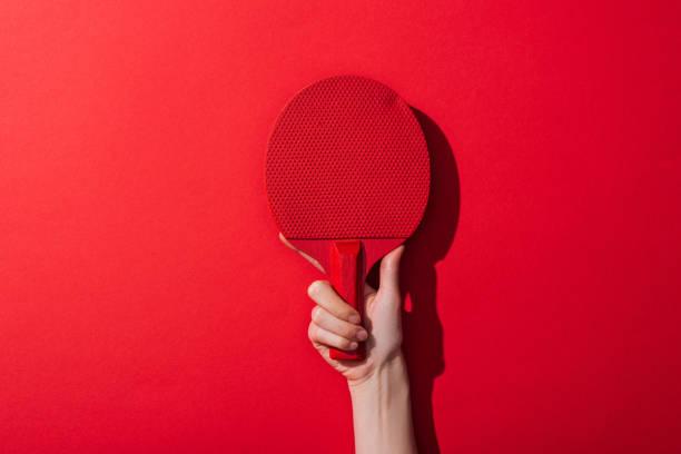cropped view of woman holding ping pong racket on red - rakietka do tenisa stołowego zdjęcia i obrazy z banku zdjęć