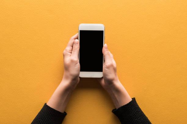 vista recortada de la mujer sosteniendo el teléfono inteligente con la pantalla en blanco sobre el fondo naranja - foto de stock