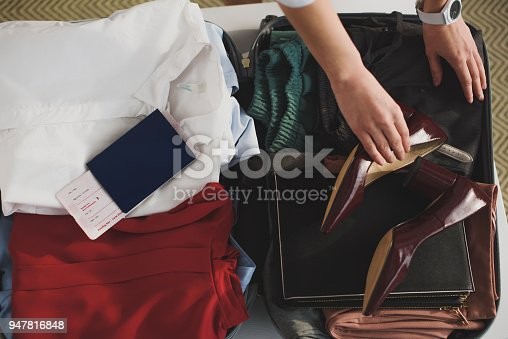 istock cropped view of woman packing clothes and passport in suitcase 947816848