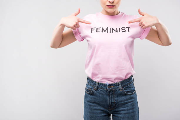 cropped view of woman pointing at pink feminist t-shirt, isolated on grey cropped view of woman pointing at pink feminist t-shirt, isolated on grey women's rights stock pictures, royalty-free photos & images