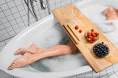 istock Cropped view of woman taking bath with foam near glass of champagne and fresh berries on tray 1291301979