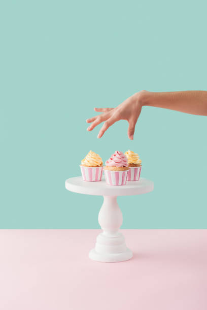 cropped view of woman taking cupcakes from cake stand cropped view of woman taking cupcakes from cake stand cakestand stock pictures, royalty-free photos & images