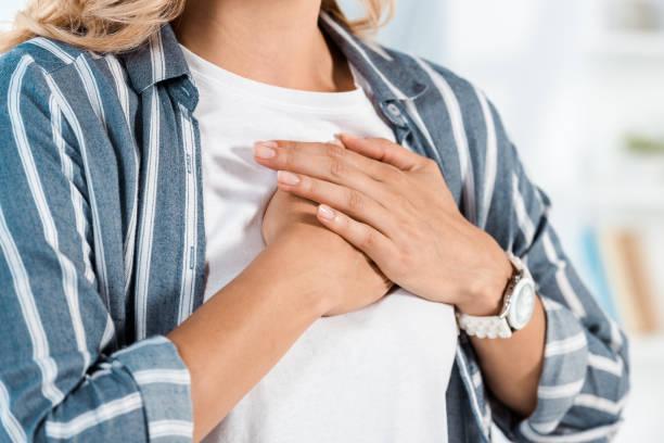 cropped view of woman touching chest at home - mão no peito imagens e fotografias de stock