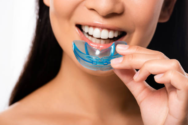 cropped view of woman using mouth guard isolated on white stock photo