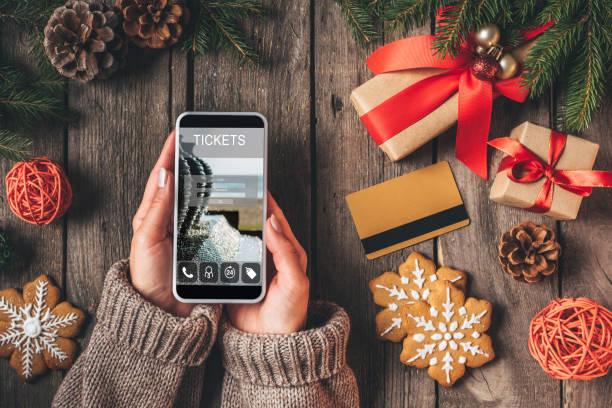 verkürzten blick auf frau mit smartphone mit ticket-app auf hölzernen hintergrund mit kreditkarte und weihnachtsgeschenke - weihnachtsprogramm stock-fotos und bilder