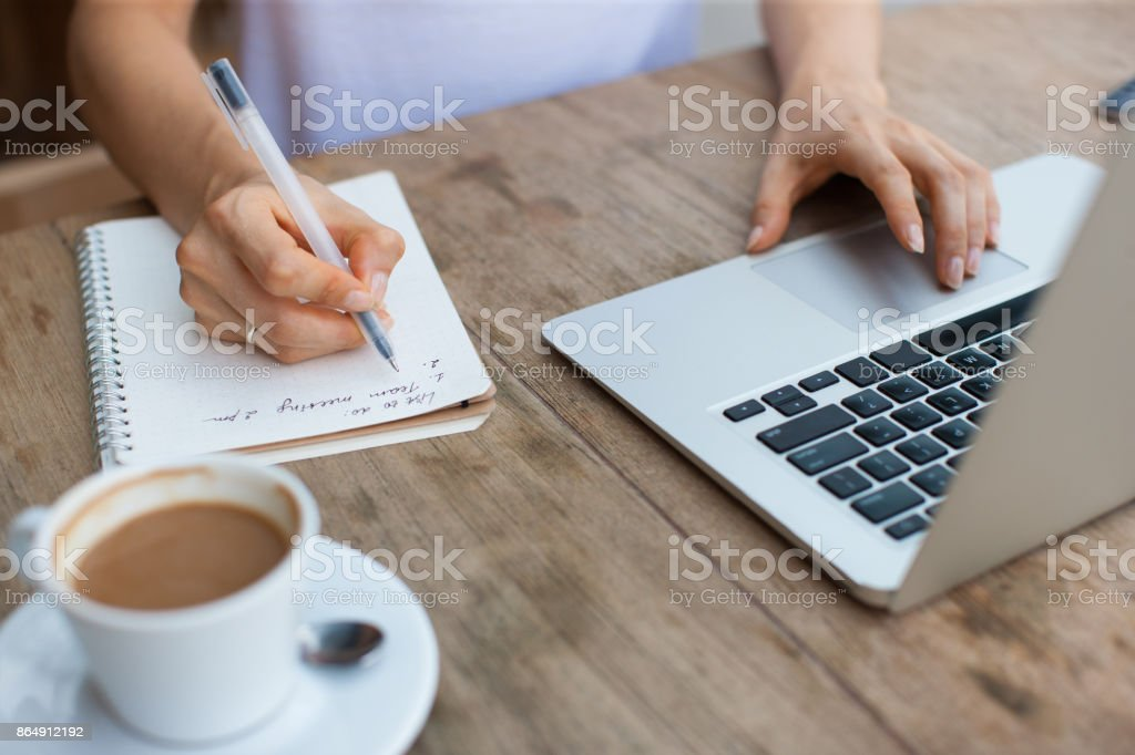Cropped View of Woman Working on Laptop in Cafe stock photo