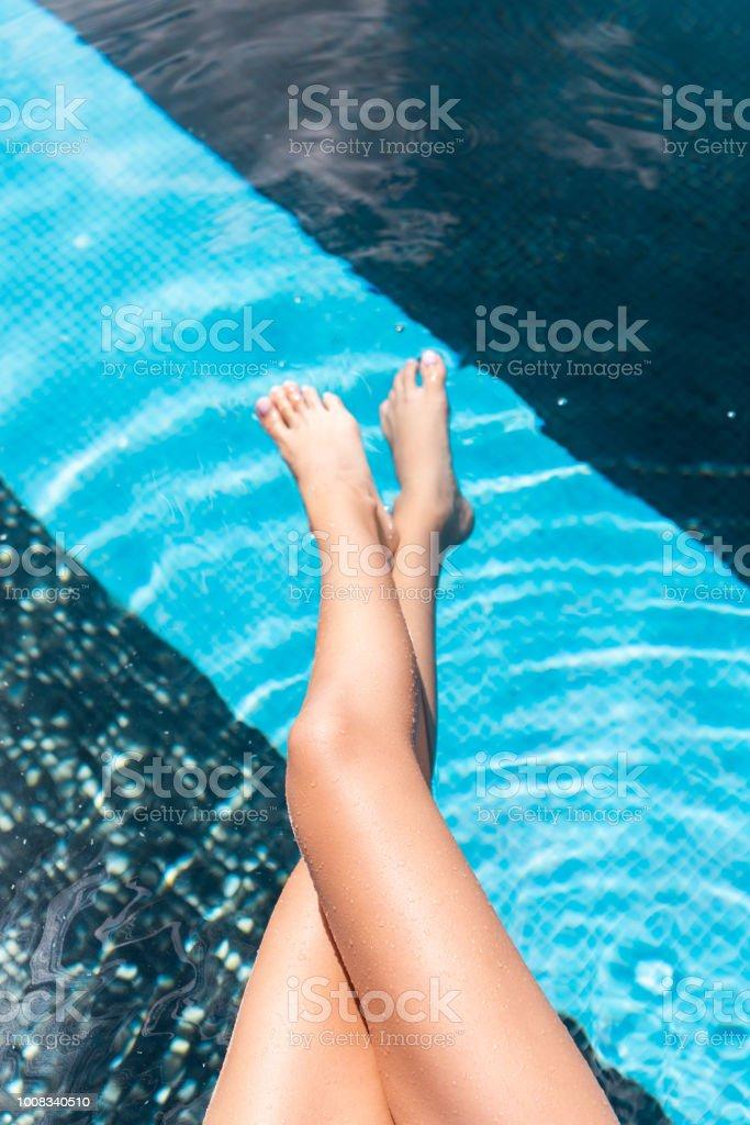 8fb87485300f03 bijgesneden weergave van dames benen in het water van het zwembad royalty  free stockfoto